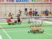 Students competing in badminton with robots they created